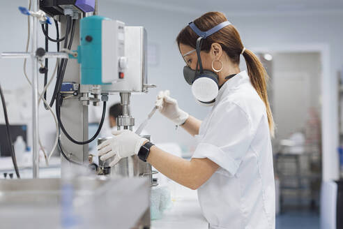 Confident female technician using medical equipment for research at lab - OCAF00514