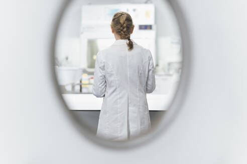 Senior female scientist seen through window at laboratory, rear view - OCAF00529