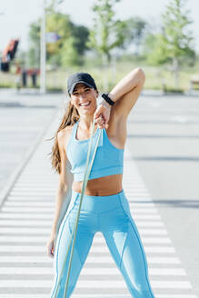 Portrait of happy young woman exercising with resistance band on sunny day - OCMF01292