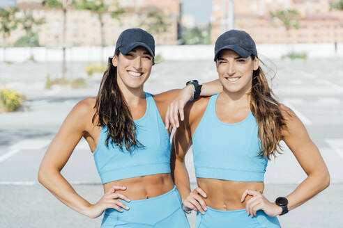 Portrait of smiling confident young twin sisters in sports clothing standing outdoors on sunny day - OCMF01307