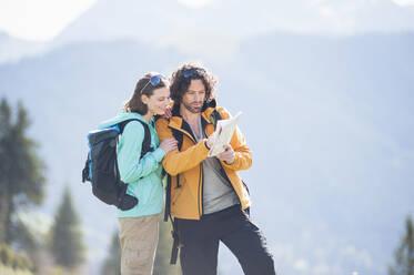 Hiking couple looking at map, Wallberg, Bavaria, Germany - DIGF11660