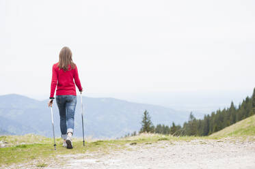 Rear view of woman with hiking poles - DIGF11678