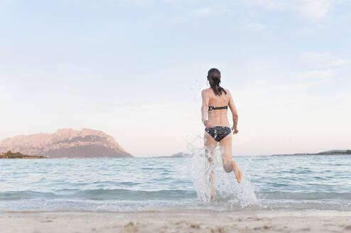 Back view of woman in bikini running into the sea, Sardinia, Italy - DIGF11720