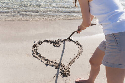 Crop view of woman on the beach  scratching heart in wet sand with wood stick, Sardinia, Italy - DIGF11744