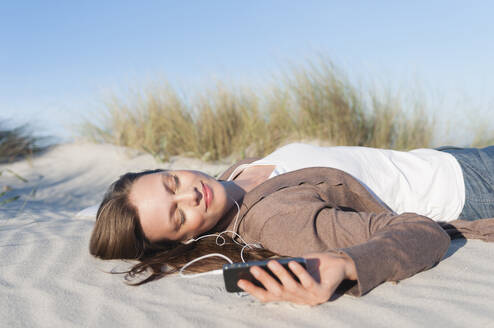 Portrait of woman lying on beach dune listening music with earphones and smartphone, Sardinia, Italy - DIGF11759