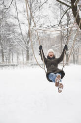 Laughing woman on swing in winter - DIGF12031
