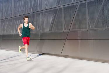Man running on sidewalk by modern building in city - DIGF12040