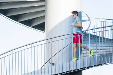 Man running on spiral staircase in city - DIGF12046