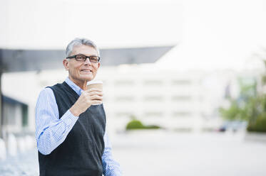 Portrait of senior businessman with coffee to go outdoors - DIGF12079