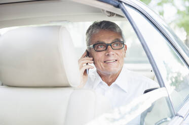 Portrait of smiling senior businessman on the phone looking out of car window car - DIGF12085