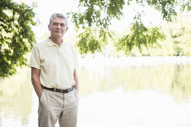 Portrait of senior man standing in a park in front of water - DIGF12088