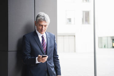 Portrait of senior businessman looking at cell phone outdoors - DIGF12091