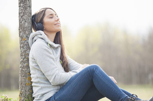 Relaxed woman listening music while leaning on tree trunk at park - DIGF12109
