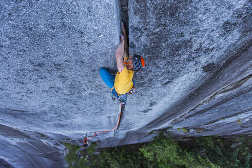 Man lead climbing off width granite climb in Squamish Canada BC - CAVF82324