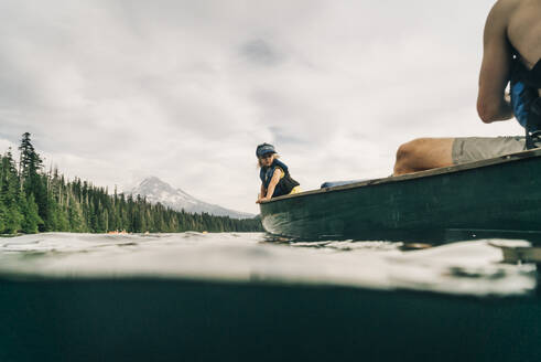 A young girl rides in a canoe with her dad on Lost Lake in Oregon. - CAVF82573