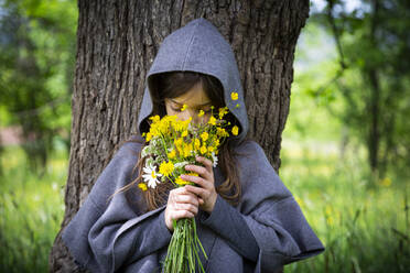 Girl smelling on bunch of yellow wildflowers - LVF08913