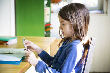 Girl doing homework and using tablet in kitchen at home - LVF08916