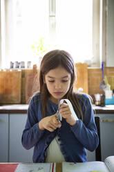 Girl cutting paper stripe during homework - LVF08919
