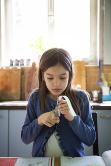 Girl cutting paper stripe during homework - LVF08919