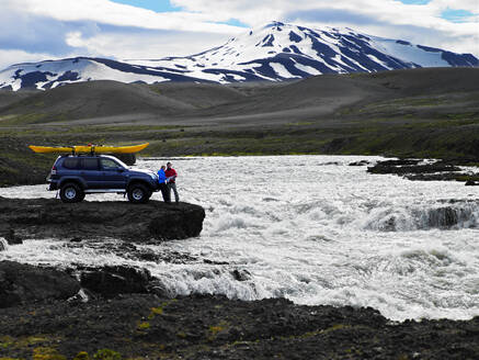 Couple reading map in front of their customised SUV in Iceland - CAVF82974