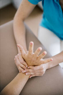 Female physiotherapist giving patient a hand massage, close up - DAWF01537