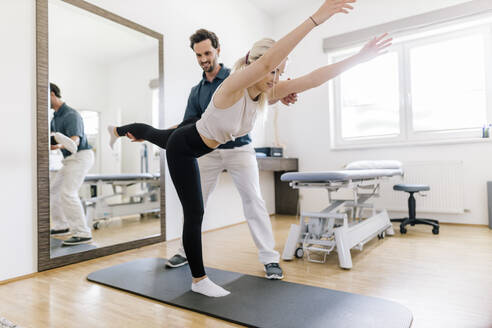 Physiotherapist assisting female patient, balancing on gym mat - DAWF01576