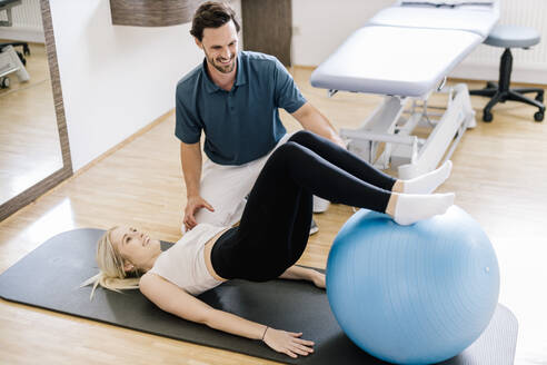 Physiotherapist assisting female patient, practicing with fitness ball, lying on gym mat - DAWF01579