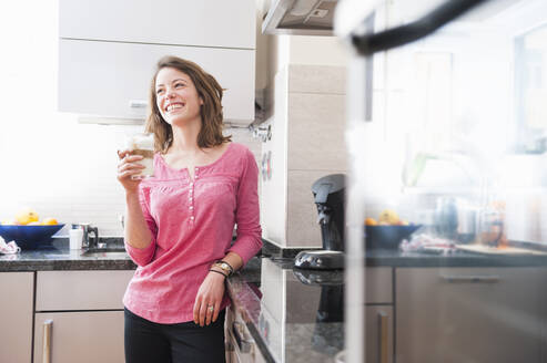 Happy woman holding glass of Dalgona coffee while standing in kitchen at home - DIGF12156
