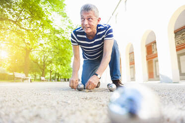 Senior boules player kneeling on the ground - DIGF12258