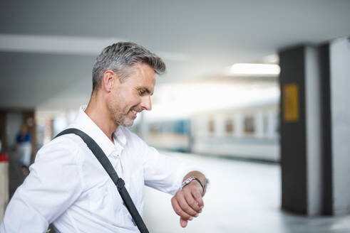 Businessman checking time while sitting at railroad station platform - DIGF12275