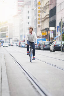 Young man riding bicycle in the city - DIGF12305