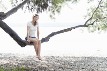 Smiling woman sitting on tree trunk at Ammersee relaxing, Germany - DIGF12410