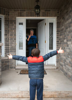 Social distance visit between young boy and his grandmother at home. - CAVF83076