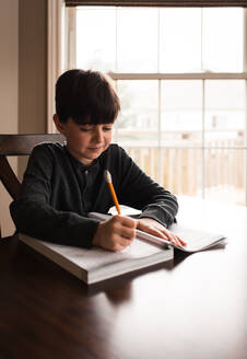 Young boy doing schoolwork in a workbook at home at the table. - CAVF83082