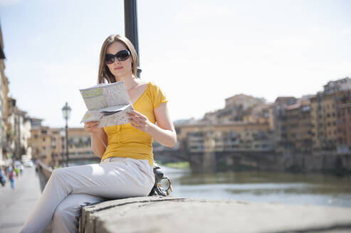 Portrait of woman sitting on a wall looking at city map, Florence, Italy - DIGF12441