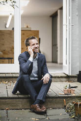 Businessman sitting in backyard, using smartphone while gardening - GUSF03825