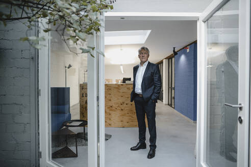 Senior businessman standing in open office door with hands in pockets - GUSF03855