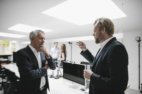 Two businessmen discussing on a meeting in office - GUSF03882