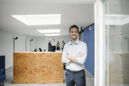 Businessman standing in open office door, people working in background - GUSF03888