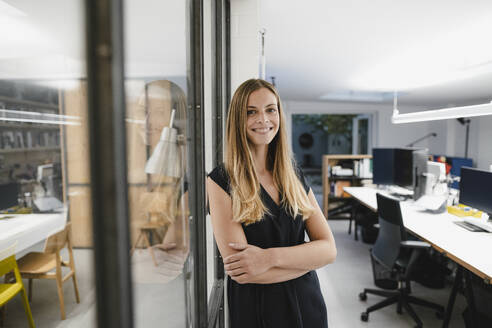 Young businesswoman standing in office, with arms crossed - GUSF03942