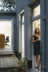 Businesswoman standing in open office door, holding cup of coffee - GUSF03954