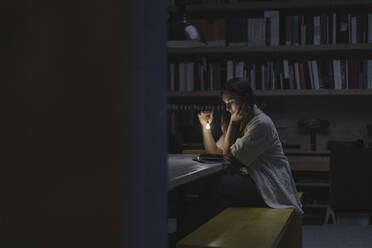Young woman sitting in office, reading book at night with a torch - GUSF03963