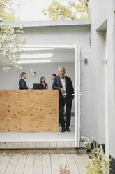 Senior businessman standing in open office door, people working in background - GUSF03996