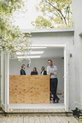 Businessman standing in open office door, people working in background - GUSF03999