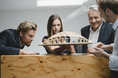 Successful business people looking at architectural model in office - GUSF04002