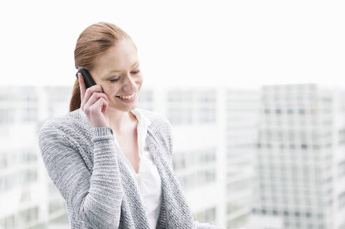 Portrait of smiling young woman on the phone outdoors - DIGF12456