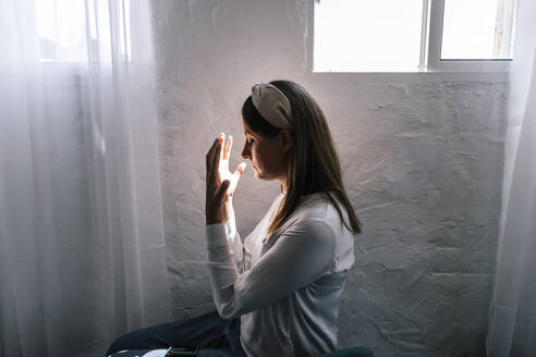 Woman praying by window at home - ERRF03856