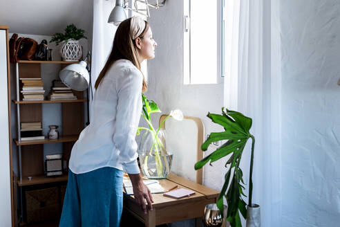 Woman looking through window while standing at desk in bedroom - ERRF03874