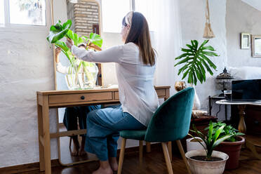 Woman arranging plants in vase while sitting on chair at home - ERRF03883