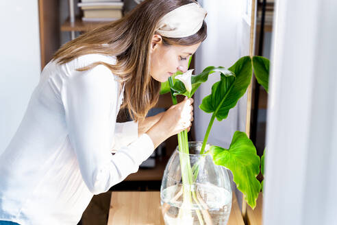 Smiling woman smelling fresh calla lily flower in glass vase at home - ERRF03889